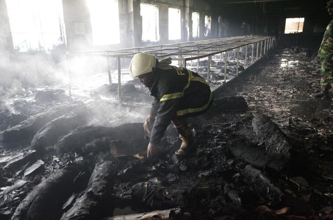 A firefighter inspects a garment factory after a devastating fire in Savar