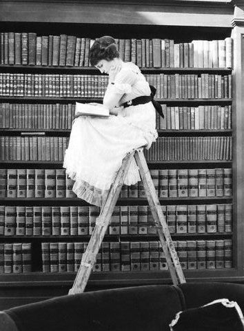 Woman reading on the top of the a ladder, 1920