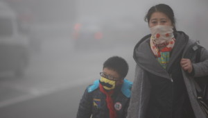 CHANGCHUN, CHINA - OCTOBER 21: (CHINA OUT) A woman and her son wearing masks walk along a road as heavy smog engulfs the city on October 21, 2013 in Changchun, China. Expressways, schools and an airport remain closed as heavy smog continues to disrupt northeast China. (Photo by ChinaFotoPress/Getty Images)