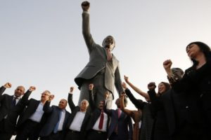 Palestinian and South African officials pose in front of a giant statue of Nelson Mandela during its inauguration ceremony in the West Bank city of Ramallah on April 26, 2016. Palestinians inaugurated the statue of Mandela donated by the South African city of Johannesburg to their political capital. The six-metre (20-foot) two-tonne bronze statue was a gift from Johannesburg with which Ramallah is twinned. / AFP PHOTO / ABBAS MOMANI